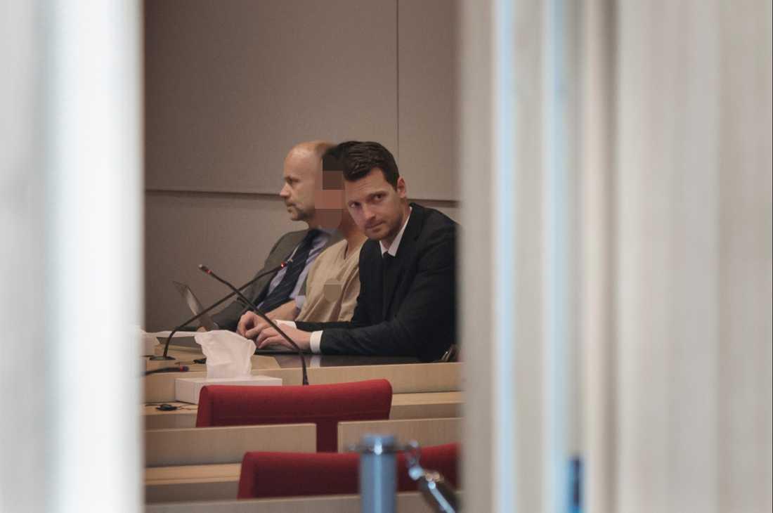 22-åringen i rättssalen tillsammans med sina försvarare Henrik Olsson Lilja och Björn Rothpfeffer.