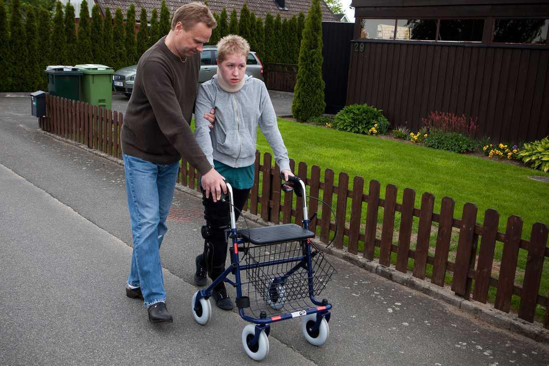 TRÄNAR MED PAPPA Emma Pettersson sitter i rullstol men tränar på att lära sig gå. När hon är hemma från sjukhuset promenerar hon med sin pappa Mats på gatan utanför villan. Hon har gjort större framsteg än läkarna vågade hoppas på och har stort stöd från både kända och okända människor. Emma har fått massor av blommor och presenter – och en dam har lovat henne en hundvalp.