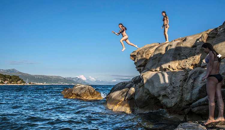 Antonia och Tonia från Split hoppar från klippan på Bacvice-stranden, strax utanför Split centrum.