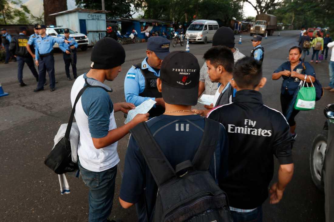 Lokal polis kontrollerar migranters dokument när de tidigt på morgonen passerar Cofradìa i Honduras på väg mot USA. Bilden är från den 15 januari 2019.