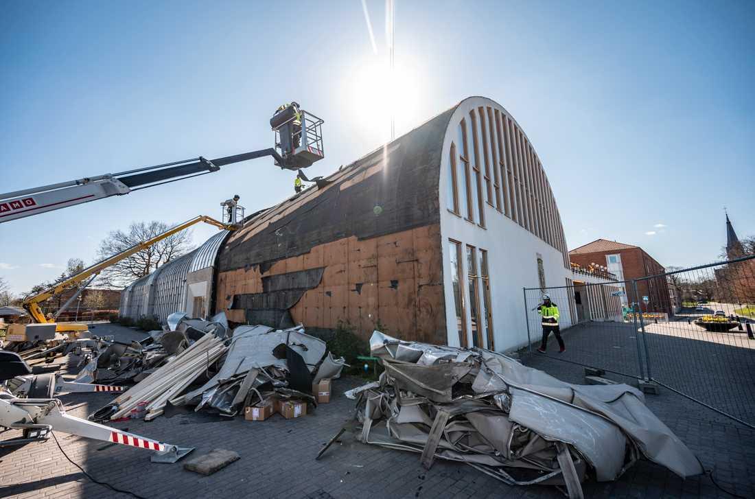 Arbete pågår med att säkra upp taket som blåst av Medborgarhuset i Eslöv i de hårda vindbyarna på torsdagen. Byggnaden som invigdes 1957 är ritad av arkitekten Hans Asplund.