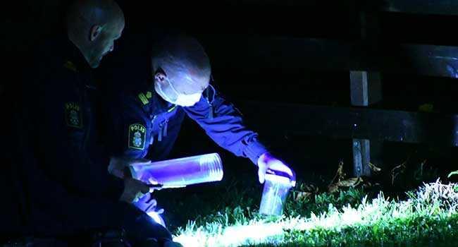 Polisens tekniker tog upp jordprover i ett grönområde.