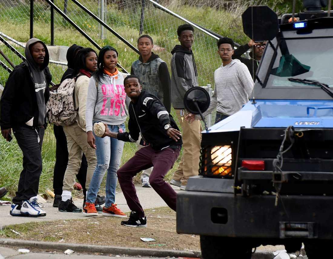 En ung kille kastar en sten mot polisen.