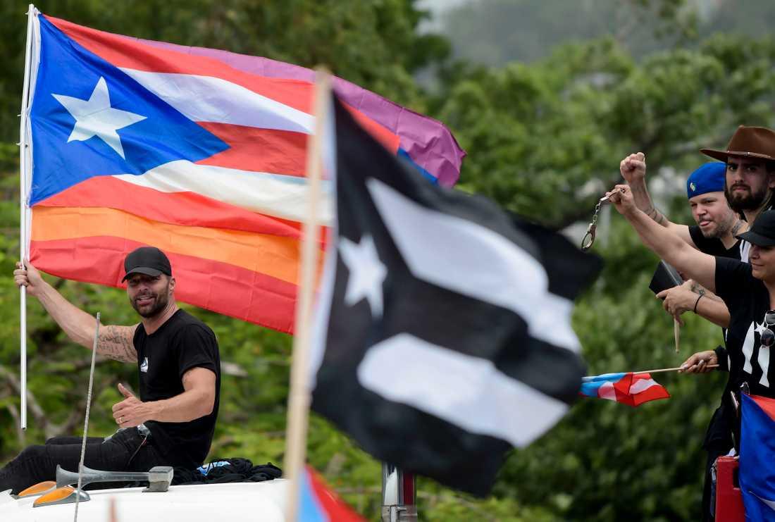 Artisten Ricky Martin håller en puertoricansk flagga under måndagens demonstration.