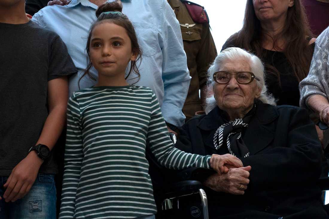 Melpomeni Dina håller en israelisk flicka i handen vid återföreningen med de judiska syskon som hon räddade under andra världskriget.