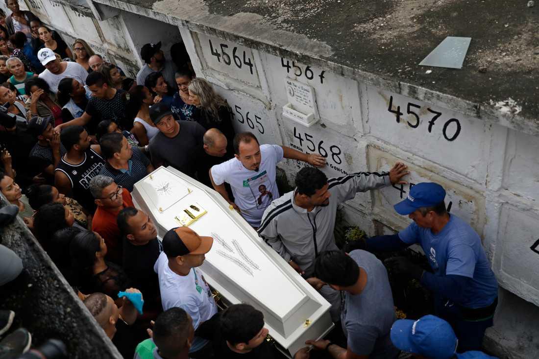 Sörjande bär fram kistan tillhörande den åttaåriga flicka som sköts ihjäl i en kåkstad i Rio de Janeiro i fredags.
