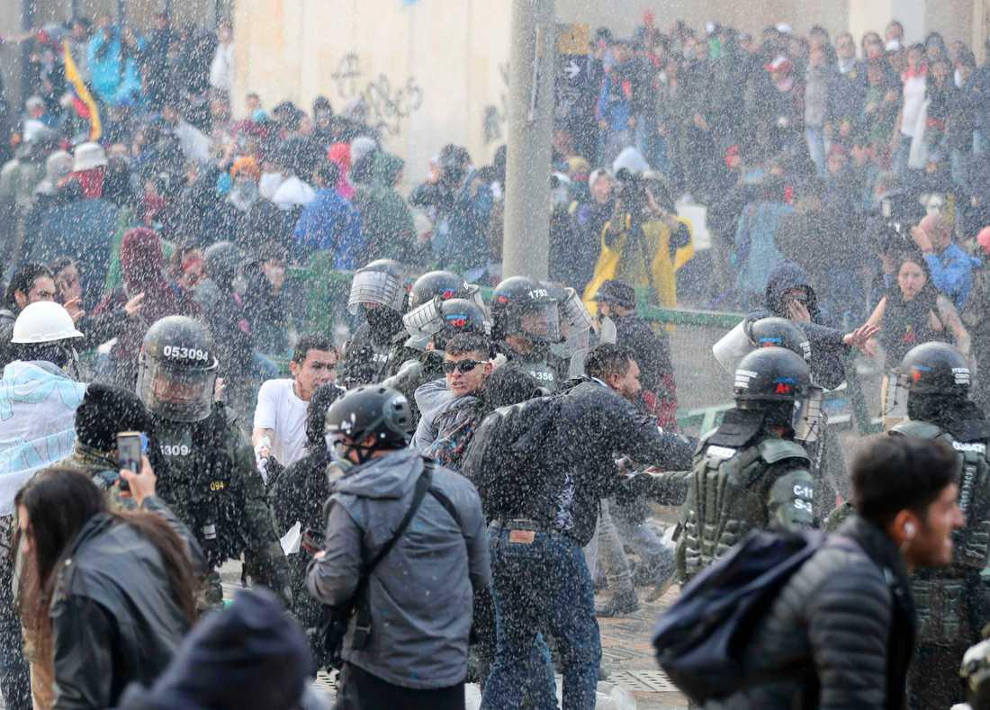 Polisen skingrar demonstranter i centrala Bogotá.