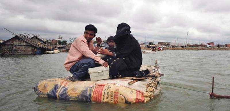 En familj räddar sig undan vattenmassorna på en improviserad flotte vid en översvämning i kåkstaden Kamragir Char i Bangladesh.