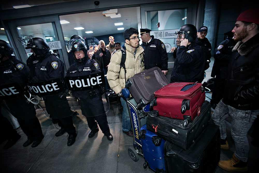 Kravallpoliser beväpnade med batonger vaktade så att bara resenärer med biljetter kunde komma in i JFK-flygplatsen.