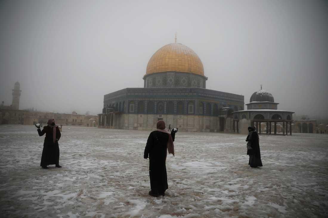 En grupp kvinnor har snöbollskrig utanför klippmoskén i Jerusalem.