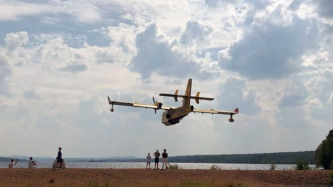 Ett italienskt brandflygplan skopar upp vatten från Orrmosjön i Härjedalen.