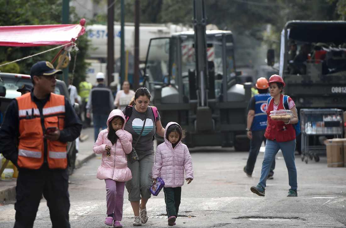 En kvinna går med två barn i närheten av skolområdet. Enligt AFP är upp mot 30 barn fortfarande saknade.