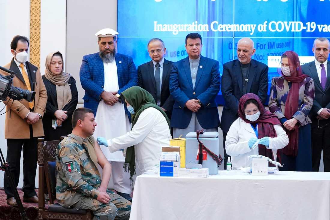 De första sprutorna med covidvaccin ges i Afghanistan, vid en ceremoni i presidentpalatset i Kabul. Tredje person från höger, som tittar på injiceringen, är president Ashraf Ghani.