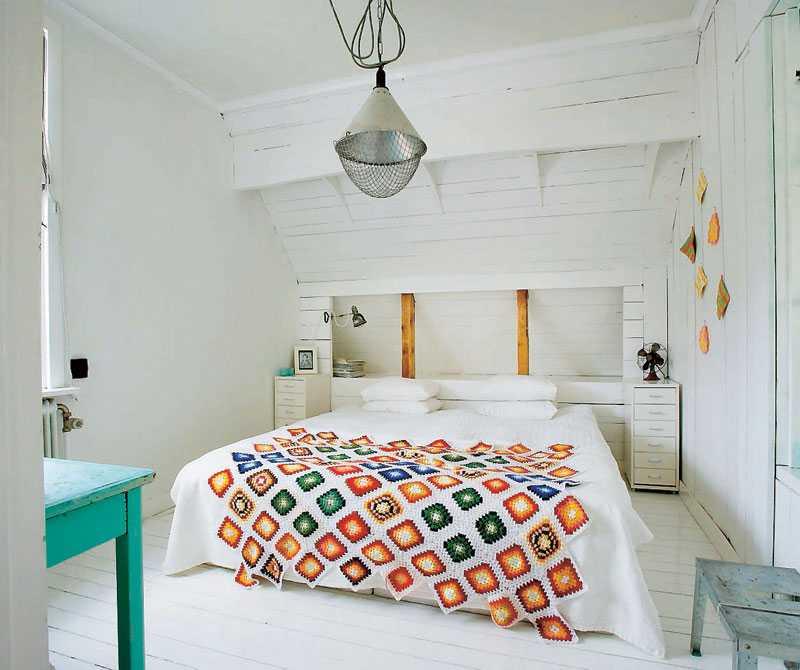 Parets sovrum är enkelt och mysigt. Ovanför sängen har de förvandlat en värmelampa för grisar till en snygg funktionell lampa och inredningsdetalj.