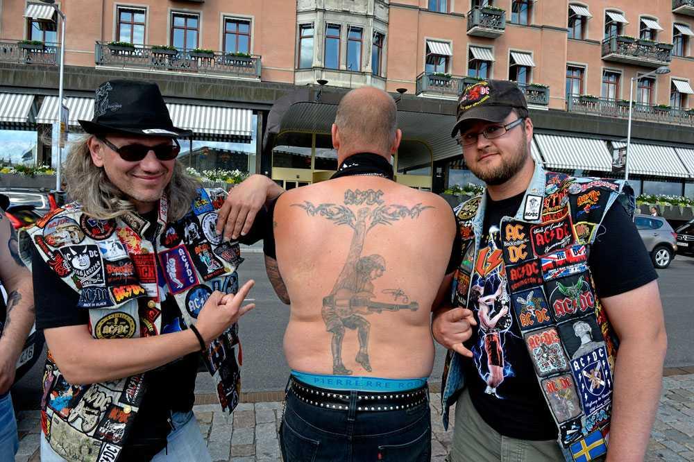 Den norske hårdrockaren Henk får hjälp av Sven från Karlsruhe och Andre från Hannover med att visa sin Angus Young-tatuering på ryggen.