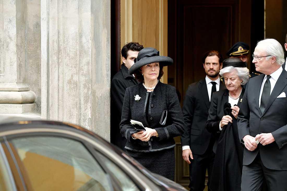 Drottning Silvia, prins Carl Philip och kungen lämnar kyrkan efter begravningen.
