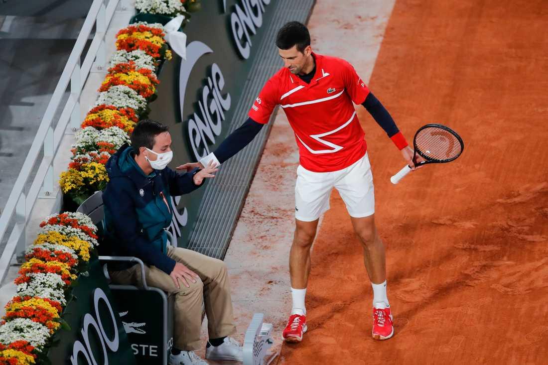 Världsettan Novak Djokovic kollar av läget med den linjedomare han råkade träffa med en boll i segermatchen mot ryssen Karen Chatjanov.