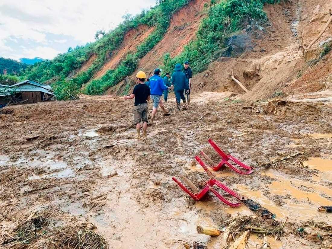 Bybor vadar genom lera efter ett jordskred i en by i distriktet Phuoc Loc i provinsen Quang Nam.
