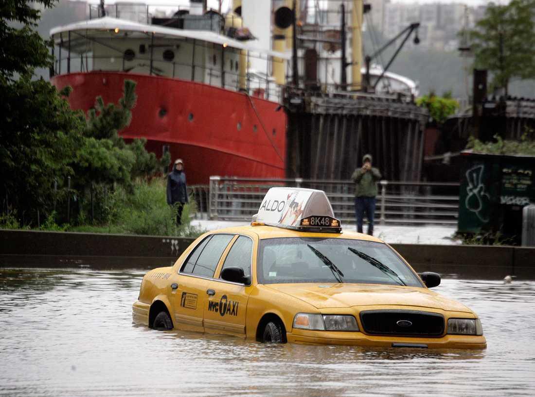 Manhattan, New York: En av New Yorks karaktäristiska taxibilar har blivit fast i vattenmassorna.