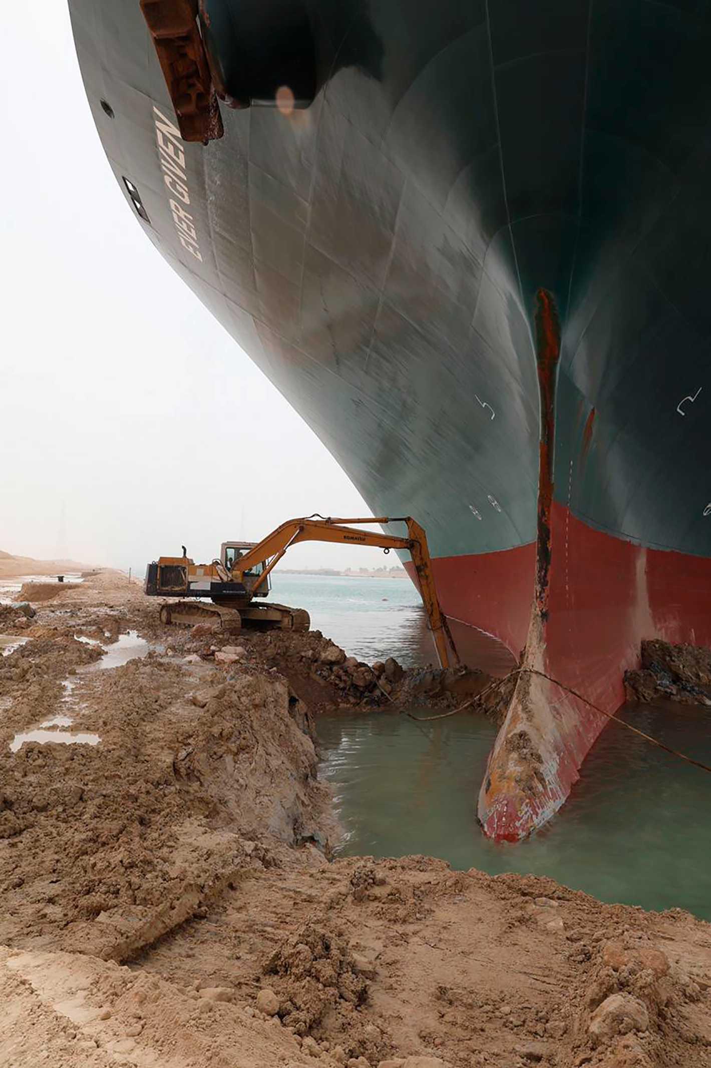 Grävskopor försöker få bort sand och gyttja runt skrovet på jättefartyget.