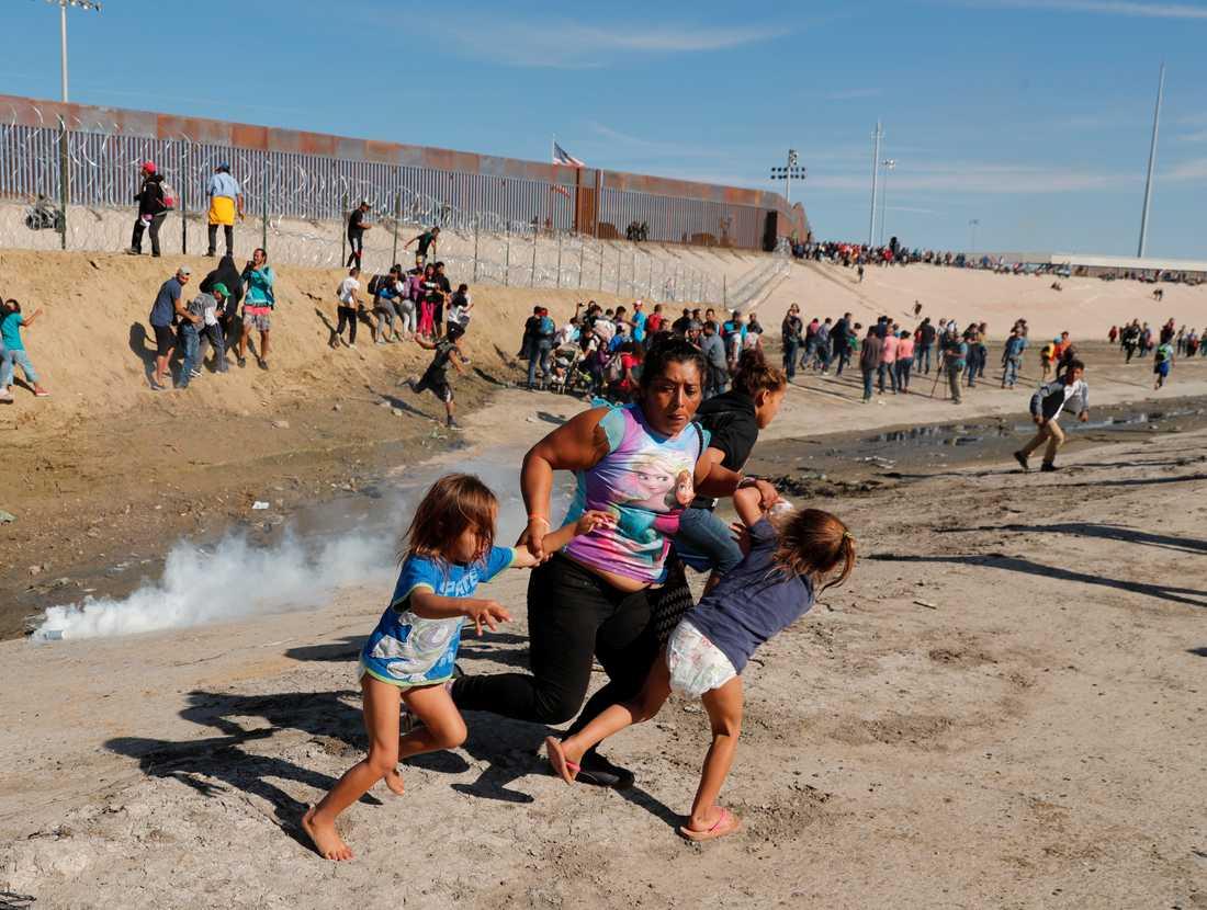 En familj springer från en tårgasbehållare som kastats över gränsen vid Tijuana.