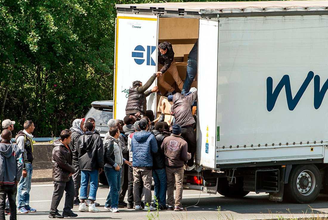Emigranter försöker ta sig ombord på en lastbil.