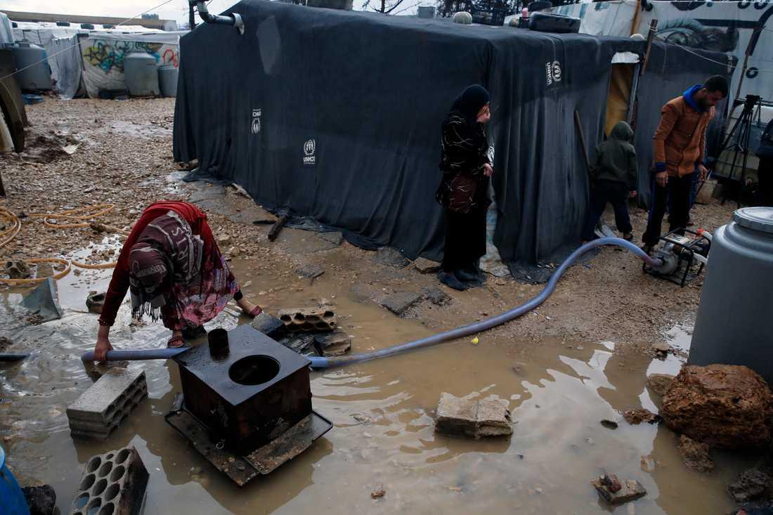 En flyktingfamilj från Syrien försöker pumpa bort vatten efter skyfall över det flyktingläger i staden Bar Elias i Libanon där de bor. Arkivbild.