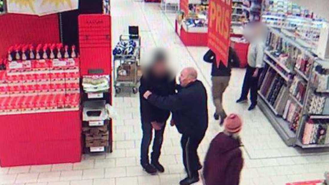 På bilder från övervakningskameran ser man ur Aksel Hansen tar tag i mannen med kniven och håller fast honom.