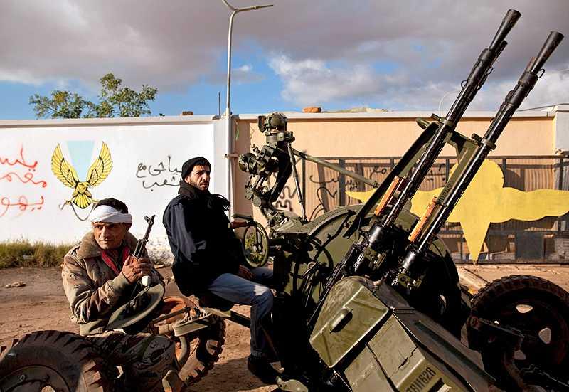 Soldater som gått över till rebellernas sida sitter på en luftvärnskanon utanför Benghazi i östra Libyen. Klicka på bilden för att se en större version.