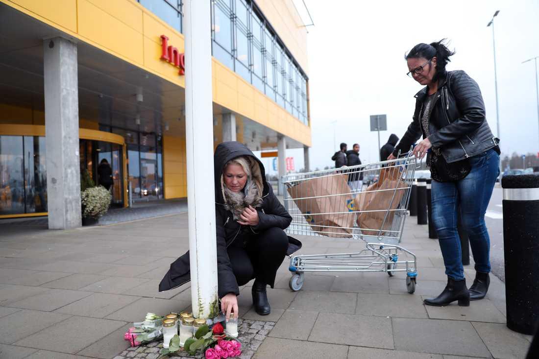 Kunder tänder ett ljus och lämnar blommor vid Ikea i Älmhult.