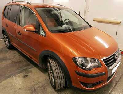 Volkswagen Touran Cross Country av årsmodell 2008, tegelröd/brunröd till färgen.