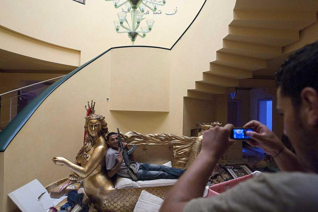 DOTTERNS SOFFA  En av rebellerna poserar framför kameran i en guldsoffa formad som en sjöjungfru i Aisha Gaddafis, dotter till Muammar Gaddafi, hem i Tripoli.