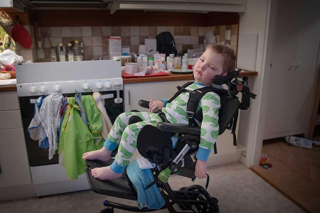 """Olof sitter fastpänd med stöd för nacken i sin  rullstol. Mycket av skötseln av Olof är medicinsk vård dygnet runt. """"Inget av det vi gör liknar normalt föräldraansvar"""", säger Karolina Hermansson."""