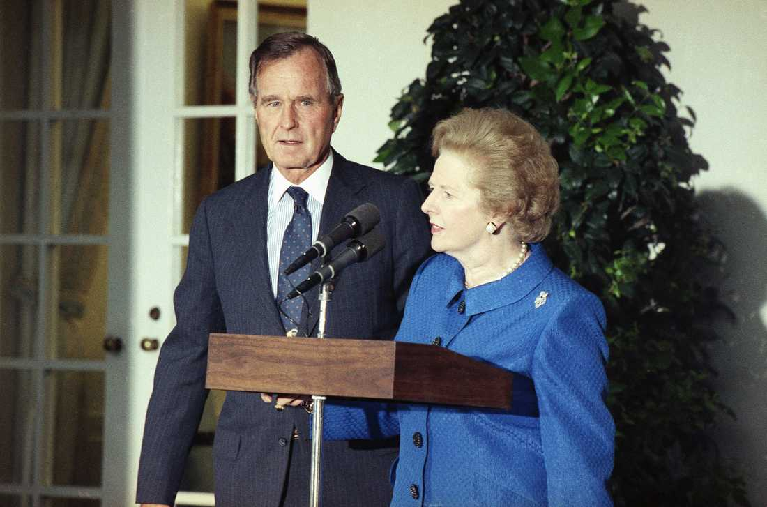 British Prime Minister Margaret Thatcher, with President Bush looking on, speaks to reporters, Monday, August 7, 1990 in Washington in the White House Rose Garden after an Oval Office meeting on the situation in the Persian Gulf. The United Nation Security Council voted 13-0 in favor of strict economic sanctions against Iraq.