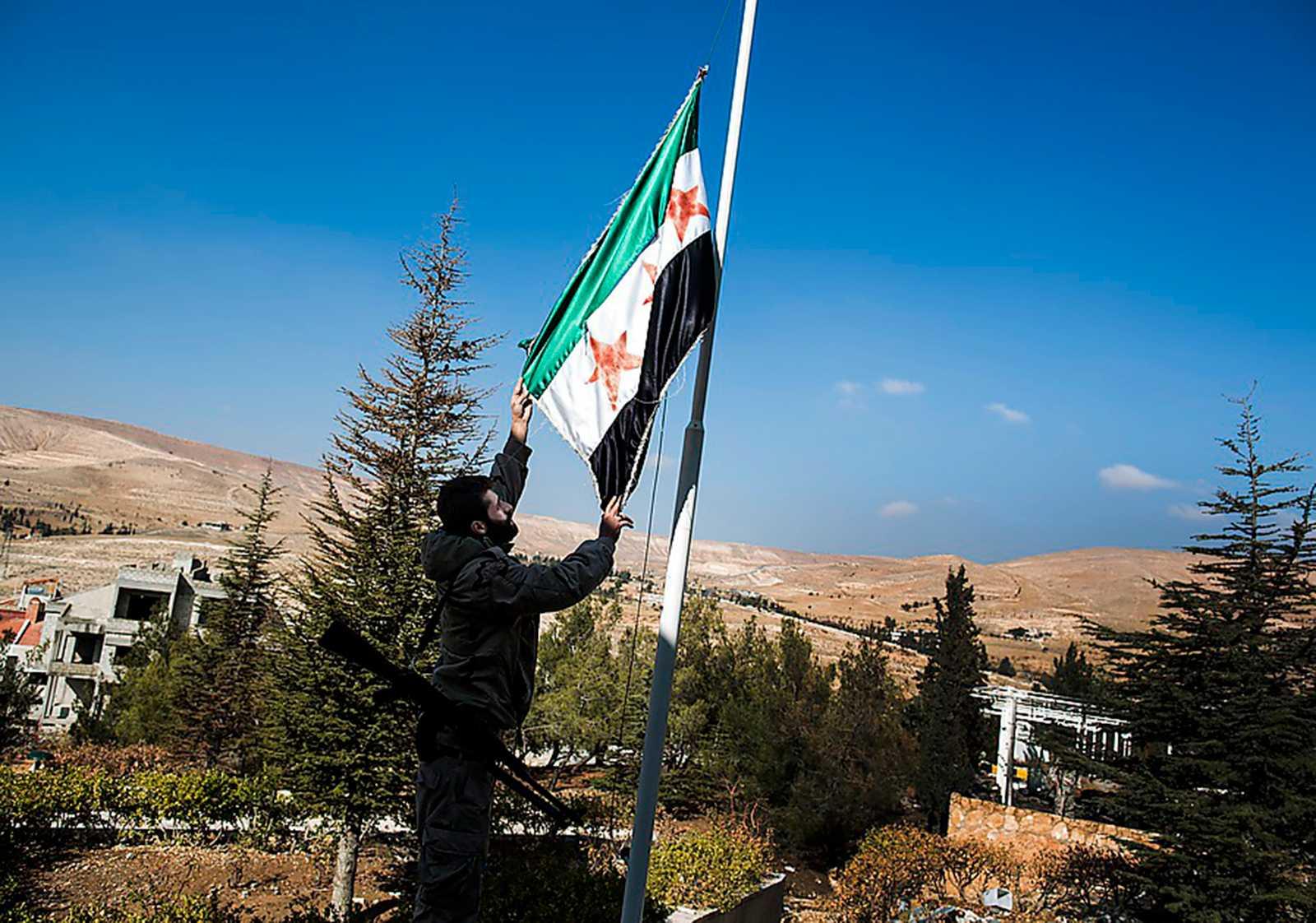 En man hissar Fria Syriska Arméns flagga i Maaloula.