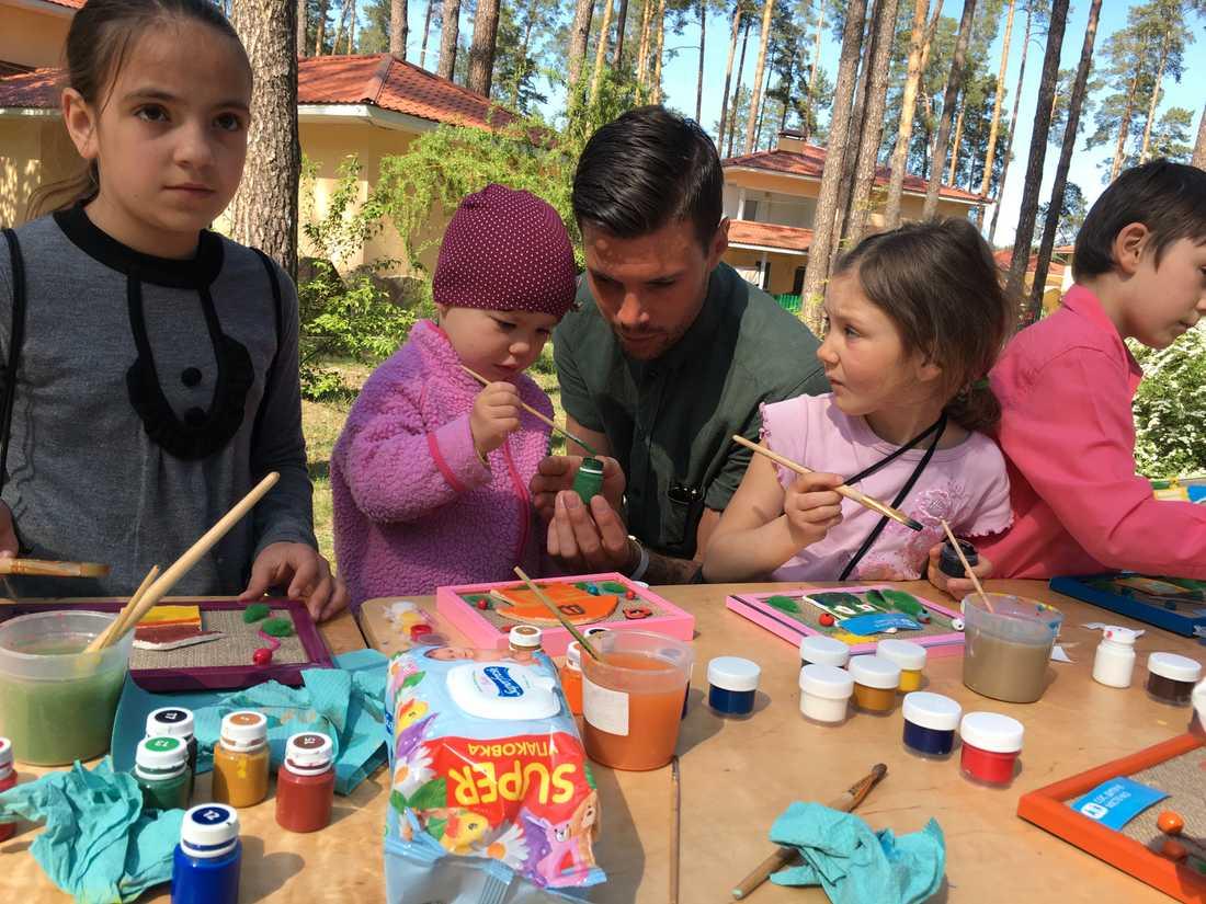 Robin Bengtsson tillsammans med några av barnen i barnbyn. Att måla används för att få barnen att uttrycka sina känslor och berätta hur de mår.