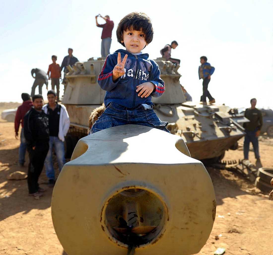 stålskelett i öknen Den lille pojken lyfts upp på kanonröret till en utbränd stridsvagn av sin pappa. Invånarna klänger på, och tar kort på, det som återstår av Gaddafis östliga pansardivision efter det franska flyganfallet.  
