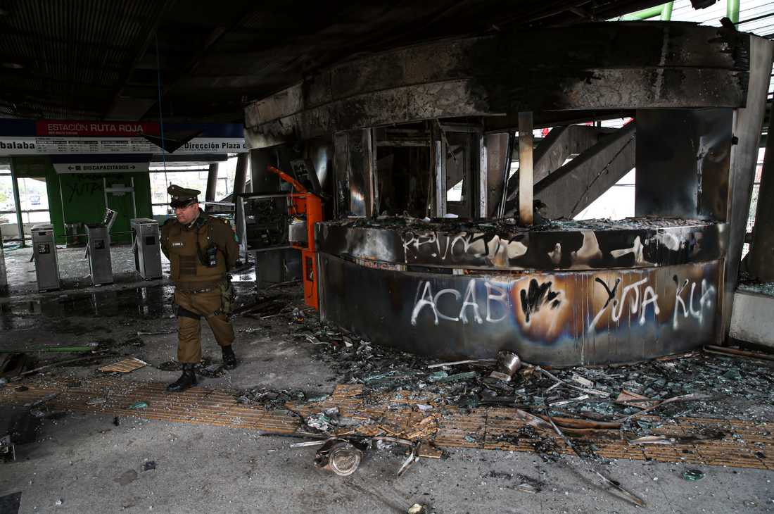 En polis vid en utbränd tunnelbanestation i Chiles huvudstad Santiago.