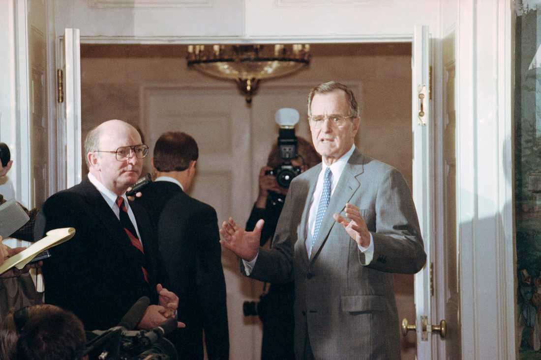 George H. W. Bush, center, responds to reporters at the White House saying he sent a personal message to Soviet President Mikhail Gorbachev to make sure the Soviets understand our position on Lithuania, Friday, March 30, 1990, Washington, D.C