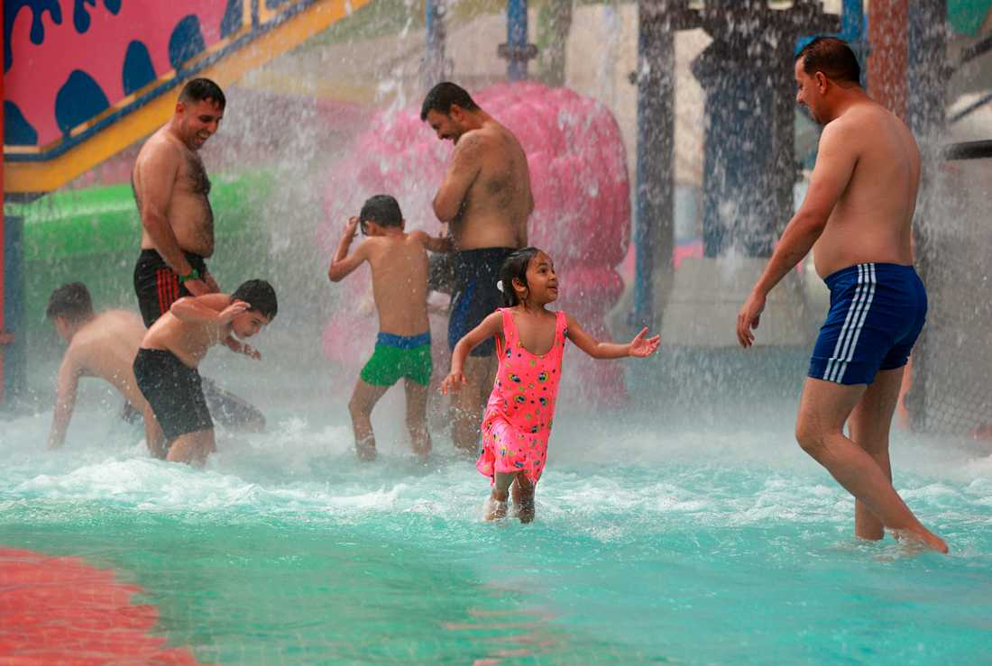 Pappor och barn svalkar sig på ett vattenland i Bagdad. Bilden är från tidigare i veckan.