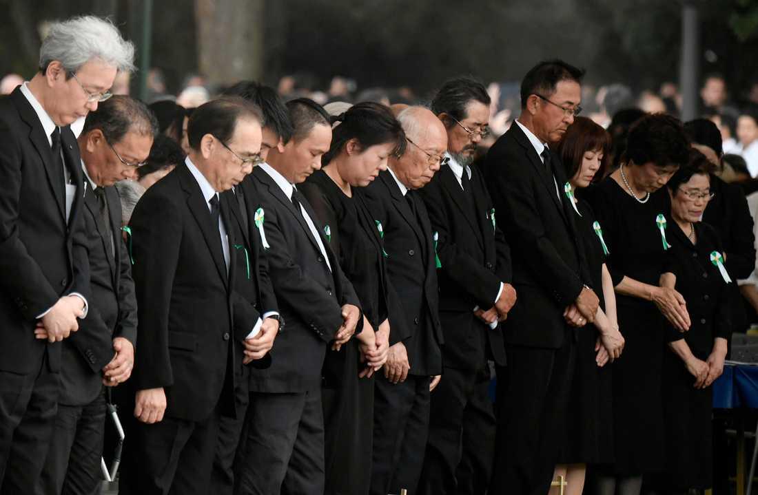 Folk hedrar atombombens offer i en tyst bön.