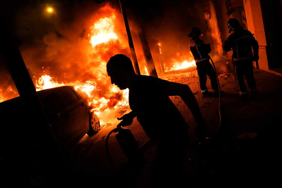 Brandmän och Barcelonabor försöker släcka brinnande bilar vid en trottoar i Barcelona.