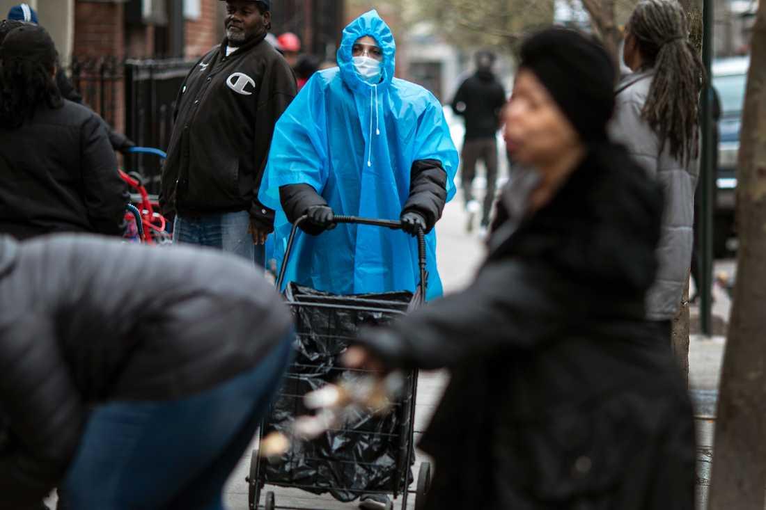 En kvinna i poncho och ansiktsmask i Brooklyn.