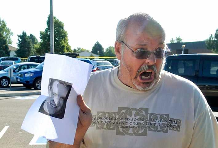Tom Sullivan håller upp ett foto på sin son Alex, som är försvunnen efter massakern.