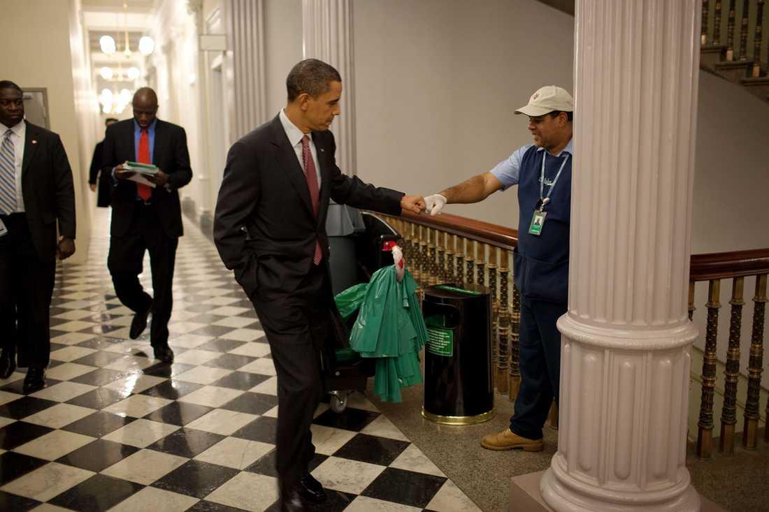 """Obama gör en """"fist-bump"""" med en vaktmästare på Eisenhower Executive Office Building."""
