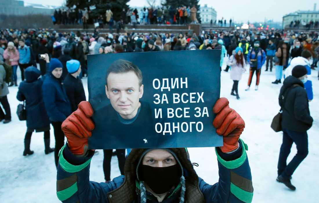 """En demonstrant med ett plakat med en bild på den fänglsade oppositionsledaren Aleksej Navalnyj och texten """"En för alla, alla för en"""" under protester i S:t Petersburg i lördags."""