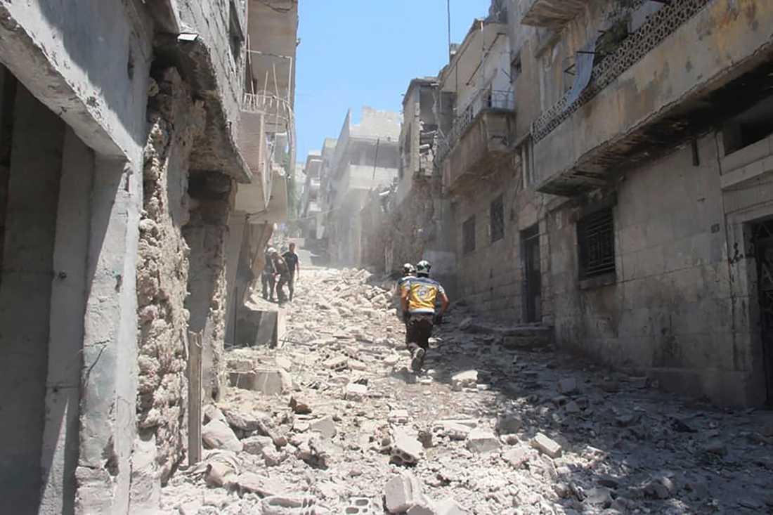 Medlemmar av den syriska organisationen Vita hjälmarna i Idlib springer genom en gata i staden Jisr al-Shugur som utsatts för en av regimens flygattacker. Arkivbild.