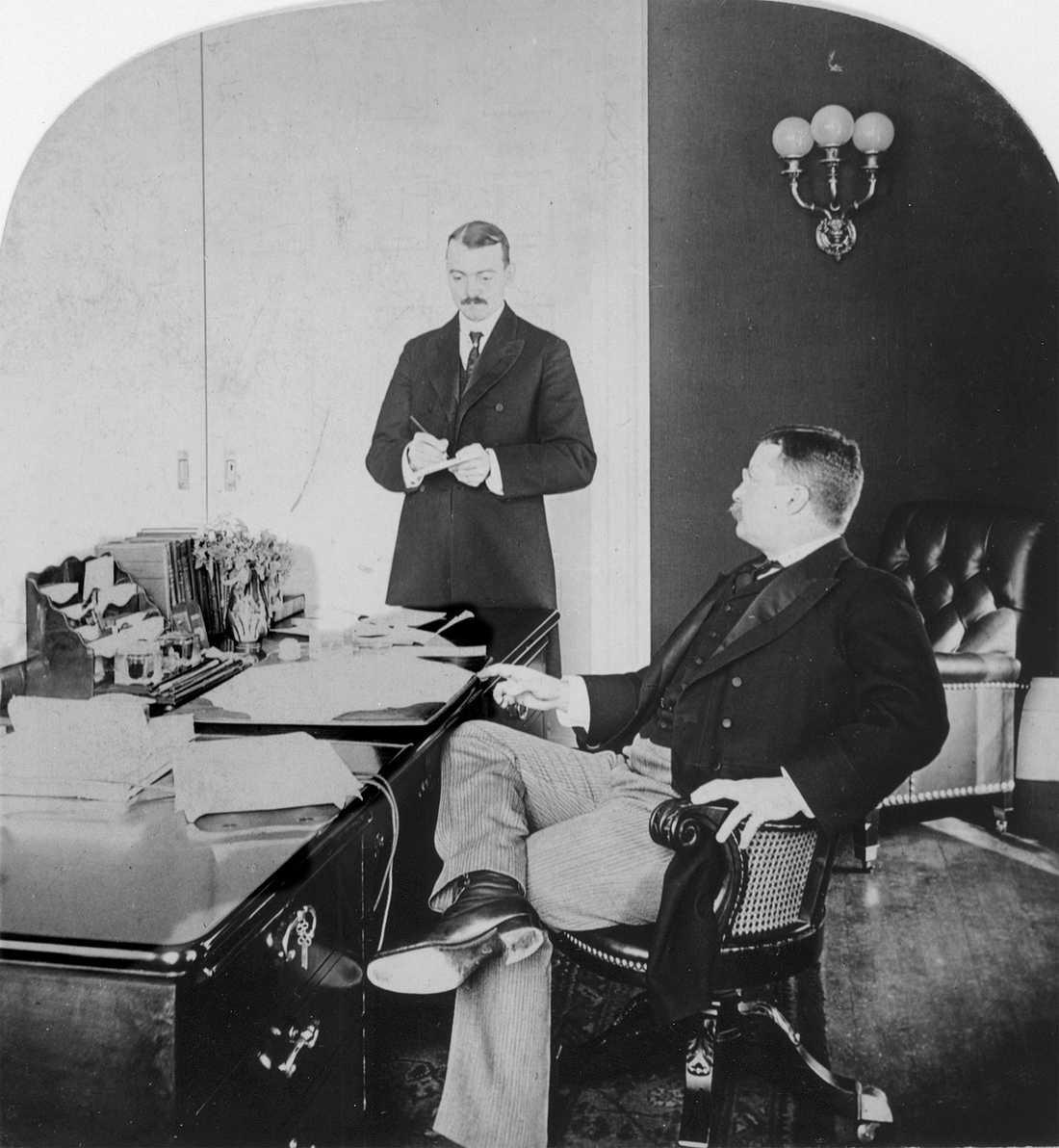 Den gamle amerikanske presidenten Theodore Roosevelt sitter bakom sitt skrivbord i Vita Huset. Här pratar han med sin privatsekreterare William Loeb Jr.