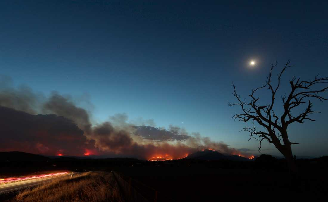 Clear Range-branden har vuxit i styrka, till följd av höga temperaturer. På bilden syns den söder om huvudstaden Canberra på fredagskvällen.