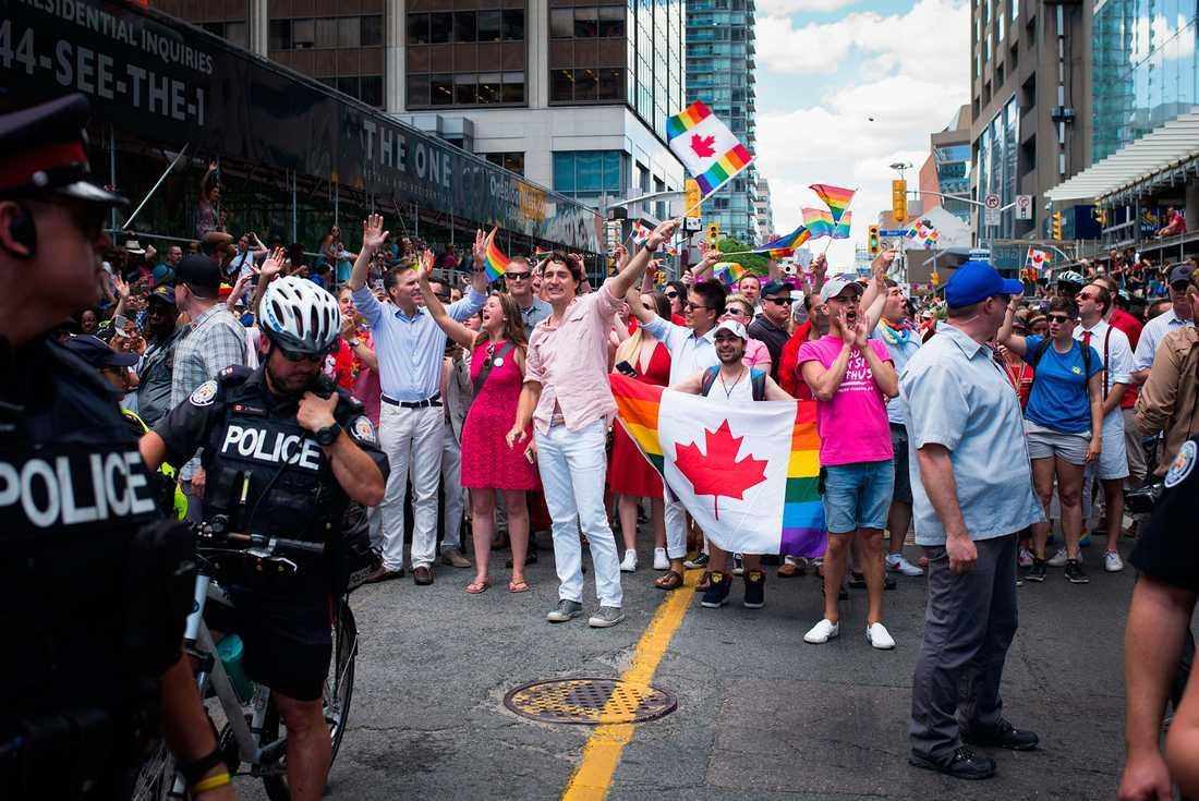 Kanadas premiärminister Justin Trudeau, ståendes i mitten, viftar med en regnbågsflagga under den årliga  Pride-festivalen i Toronto, Kanada, den 3 juli.